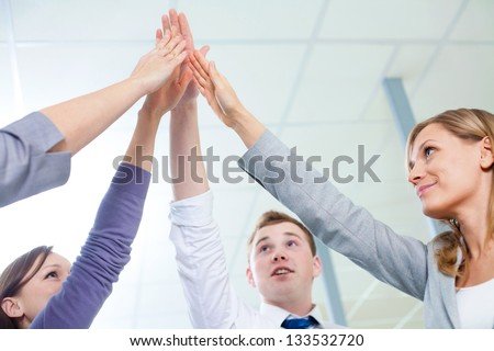 Cropped image of business people hands giving high five - stock photo