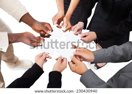 Cropped image of business people's hands solving jigsaw puzzle over white background