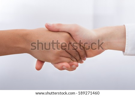 Cropped image of business people shaking hands at desk - stock photo