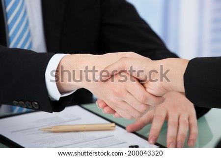 Cropped image of business people shaking hands over white background - stock photo