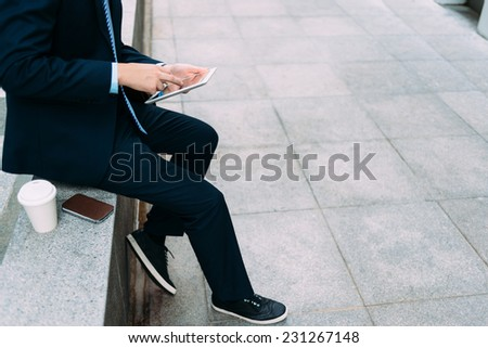 Cropped image of business person sitting outdoors and using digital tablet - stock photo