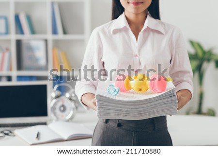 Cropped image of business woman holding stack of documents and baby toys on the top of it - stock photo