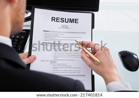 Cropped image of businessman analyzing resume at desk in office - stock photo