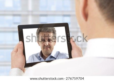 Cropped image of businessman attending video conference with colleague on digital tablet - stock photo