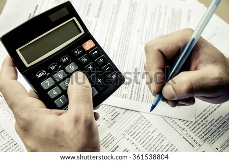 Cropped image of  Businessman calculating and checking tax. toned image - stock photo