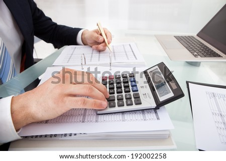 Cropped image of businessman calculating expense at desk in office - stock photo
