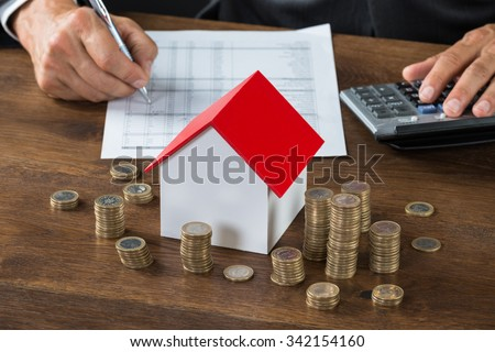 Cropped image of businessman calculating tax by model house and stacks of coins on table - stock photo