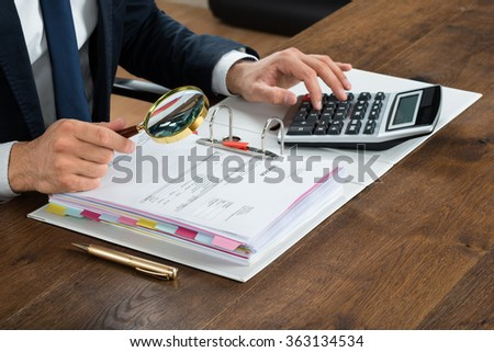 Cropped image of businessman checking invoice with magnifying glass at desk - stock photo