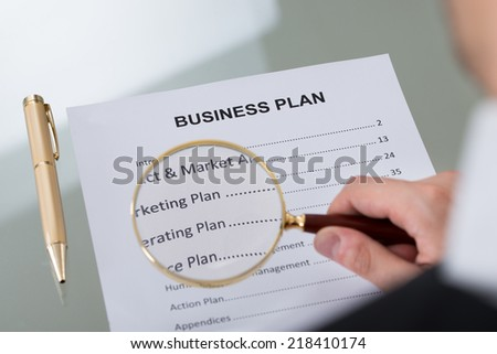 Cropped image of businessman examining business plan document with magnifying glass at desk - stock photo