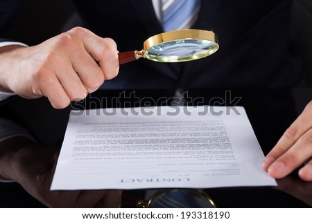 Cropped image of businessman examining contract paper with magnifying glass at desk - stock photo