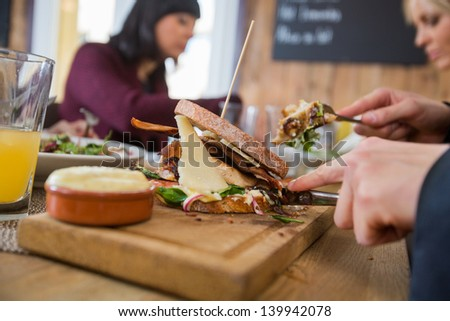 Cropped image of businessman having burger with colleagues at restaurant