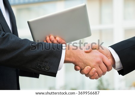 Cropped image of businessman holding digital tablet while shaking hand with partner outdoors