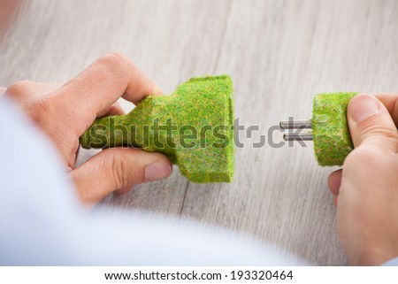Cropped image of businessman holding grass covered electric plug and socket at desk in office - stock photo