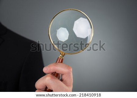 Cropped image of businessman holding magnifying glass against gray background - stock photo