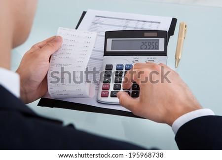Cropped image of businessman holding receipt while calculating expense at desk in office - stock photo