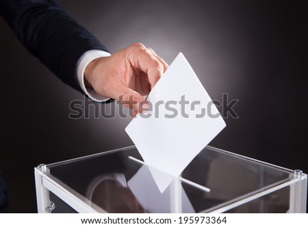 Cropped image of businessman inserting ballot in box on desk against black background - stock photo