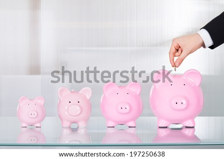 Cropped image of businessman inserting coin in piggybank at desk in office - stock photo