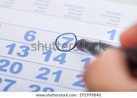 Cropped image of businessman marking date on calendar in office - stock photo