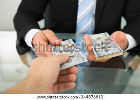 Cropped image of businessman passing money to colleague at table - stock photo