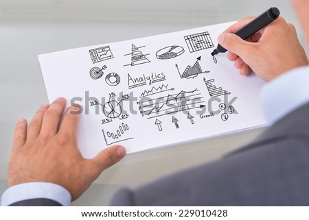 Cropped image of businessman preparing analytical diagrams at table in office - stock photo