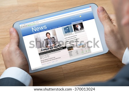 Cropped image of businessman reading news on digital tablet at office desk - stock photo