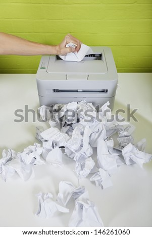 Cropped image of businessman's hand using printer with paper balls on desk - stock photo
