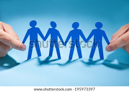 Cropped image of businessman's hands holding paper people chain on desk