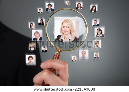 Cropped image of businessman searching candidate with magnifying glass over gray background - stock photo