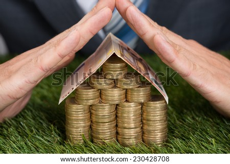Cropped image of businessman shielding house made from coins and euro note on grass - stock photo