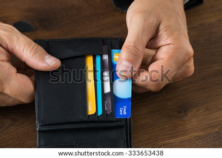 Cropped image of businessman showing credit card in wallet at desk - stock photo