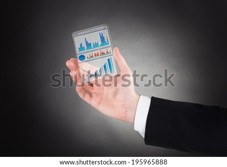 Cropped image of businessman showing graphs on modern smartphone against black background
