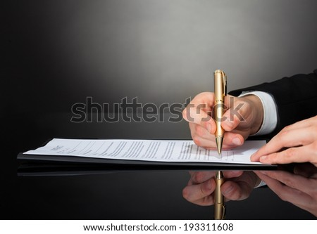 Cropped image of businessman signing document at desk against black background - stock photo