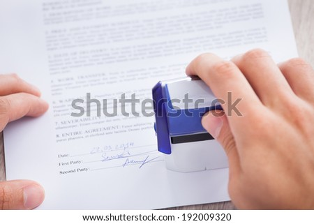 Cropped image of businessman stamping contract paper on table - stock photo