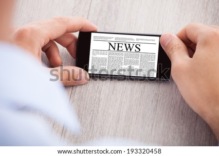 Cropped image of businessman surfing news on smartphone at desk - stock photo