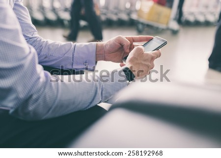 Cropped image of businessman texting while waiting at the airport - stock photo