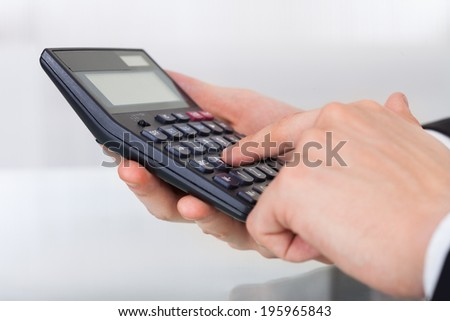 Cropped image of businessman using calculator in office