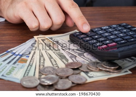 Cropped image of businessman using calculator with coins and banknotes on desk - stock photo