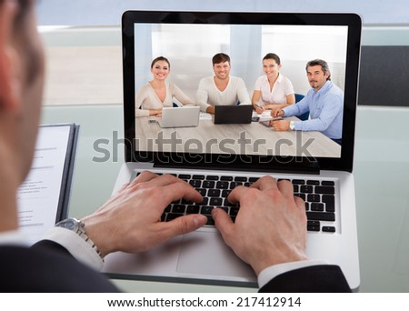 Cropped image of businessman using laptop at desk in office - stock photo