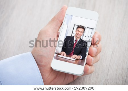 Cropped image of businessman video conferencing with colleague at desk - stock photo