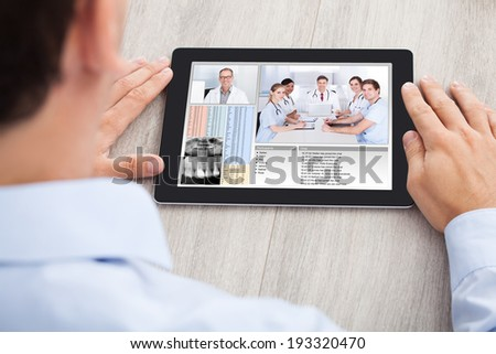 Cropped image of businessman video conferencing with medical team on digital tablet at desk in office - stock photo