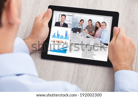 Cropped image of businessman video conferencing with team on digital tablet at desk in office - stock photo