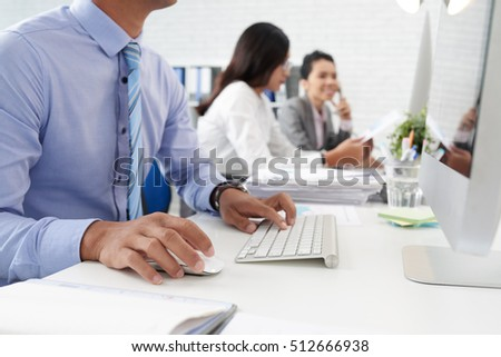 Cropped image of businessman working on computer in office