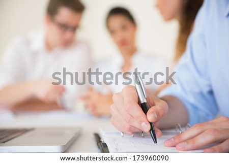 Cropped image of businessman writing in diary at office meeting - stock photo