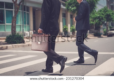 Cropped image of businessmen crossing the road - stock photo