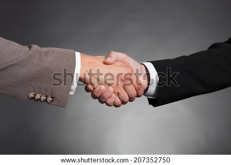 Cropped image of businessmen shaking hands against black background - stock photo