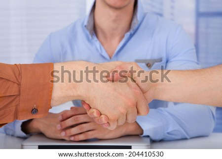 Cropped image of businessmen shaking hands in front of male colleague at office - stock photo