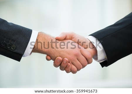 Cropped image of businessmen shaking hands outdoors