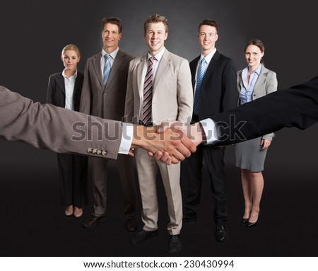 Cropped image of businessmen shaking hands with confident team standing behind over gray background - stock photo