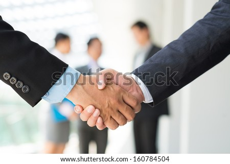 Cropped image of businesspeople handshaking in the sign of agreement on the foreground - stock photo