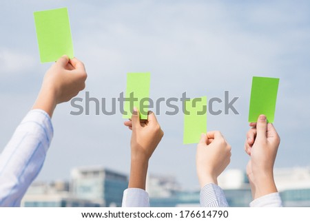 Cropped image of businesspeople holding positive green cards in the sign of approval